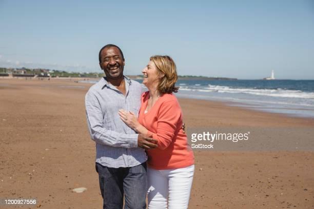 happy senior couple enjoying romantic along coast - 60 69 years stock pictures, royalty-free photos & images