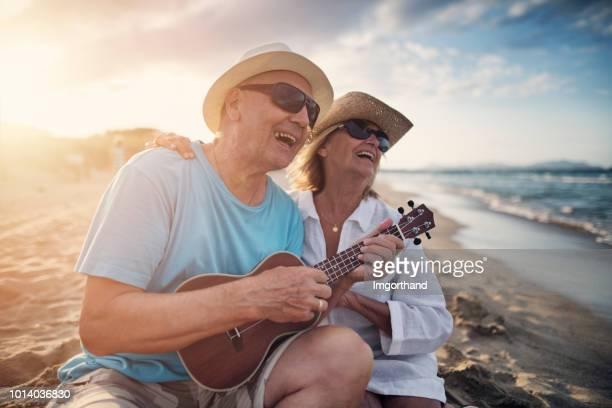happy senior couple enjoying sunset on beach - ukulele stock pictures, royalty-free photos & images