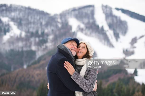 Happy senior couple face to face in winter landscape looking up