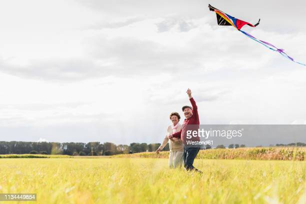 happy senior couple flying kite in rural landscape - young at heart stock pictures, royalty-free photos & images