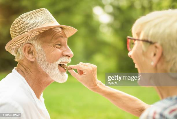 happy senior couple having a picnic in nature and eating chocolate. - couple chocolate stock pictures, royalty-free photos & images