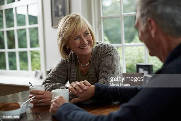 happy senior couple having coffee in cottage - 60 69 jaar stockfoto's en -beelden