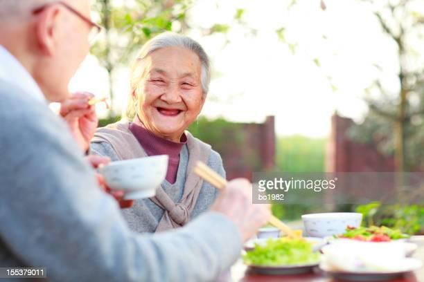 happy senior couple having dinner in the yard