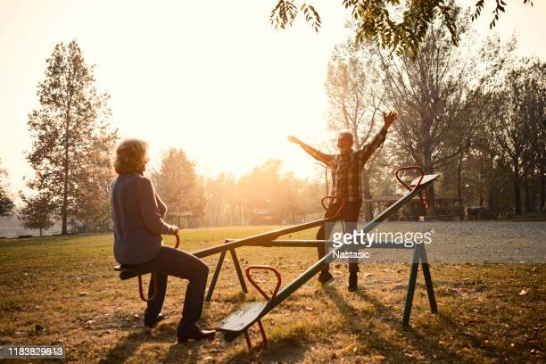 happy senior couple having fun at the playground ,riding seesaw - seesaw stock pictures, royalty-free photos & images