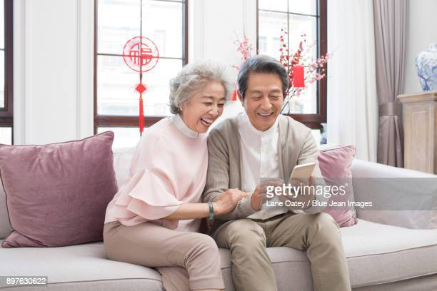 happy senior couple having video chat on smart phone during chinese new year - 70 year old man stock pictures, royalty-free photos & images