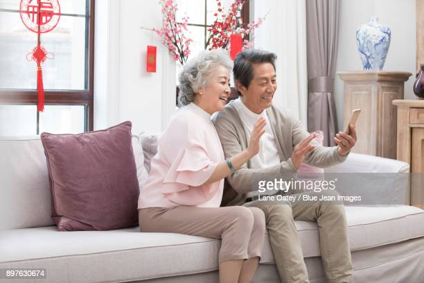 Happy senior couple having video chat on smart phone during Chinese New Year