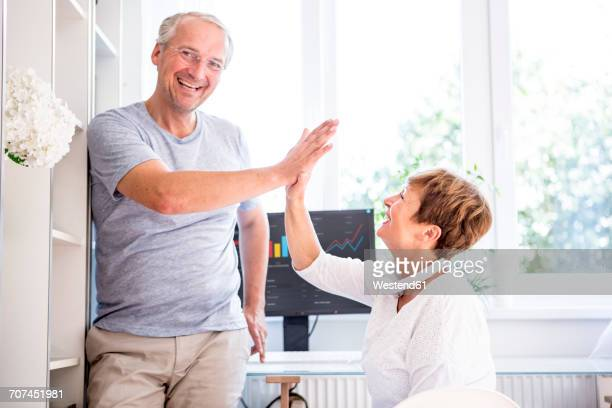 Happy senior couple high fiving in front of computer screen with charts