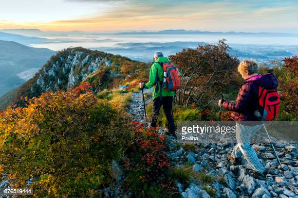 happy senior couple hiking at autumnal dawn in julian alps, slovenia, europe - slovenia stock pictures, royalty-free photos & images