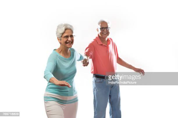 happy senior couple holding hands and dancing  - indian couples stock pictures, royalty-free photos & images