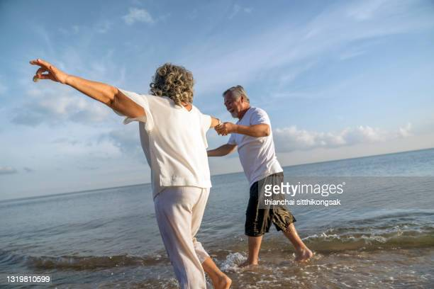 happy senior couple  holding hands and enjoying retirement lifestyle having fun walking on the beach. - married stock pictures, royalty-free photos & images