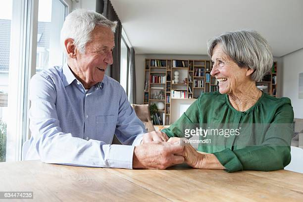 Happy senior couple holding hands at home
