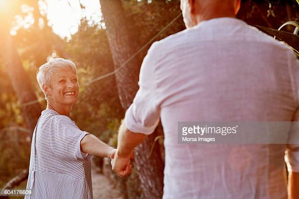 Happy senior couple holding hands in forest