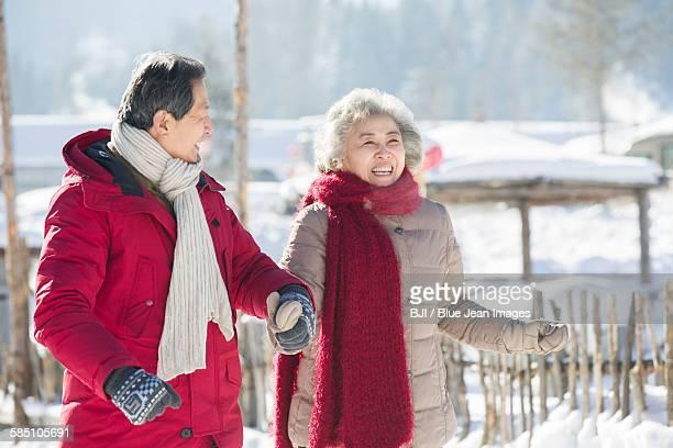 Happy senior couple holding hands walking