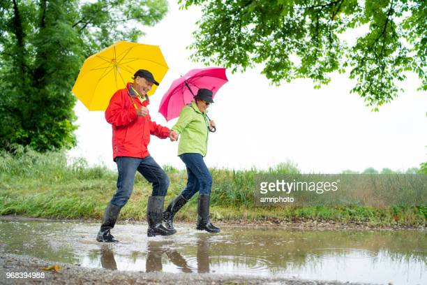 happy senior couple in black rubber boots taking a walk on rainy day - skipping along stock pictures, royalty-free photos & images