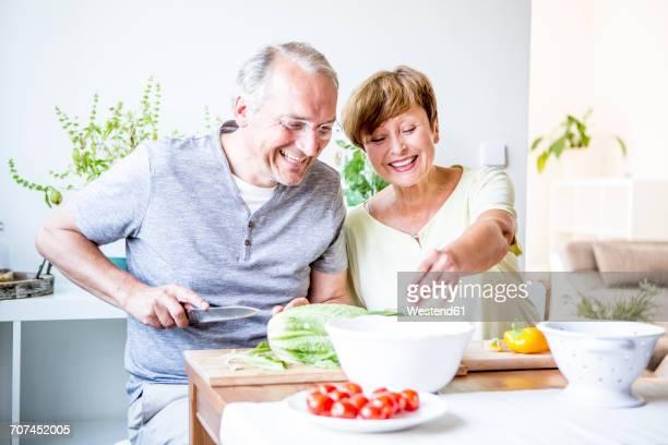 Happy senior couple in kitchen preparing salad together