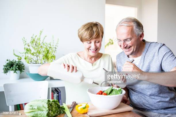 Happy senior couple in kitchen preparing salad together
