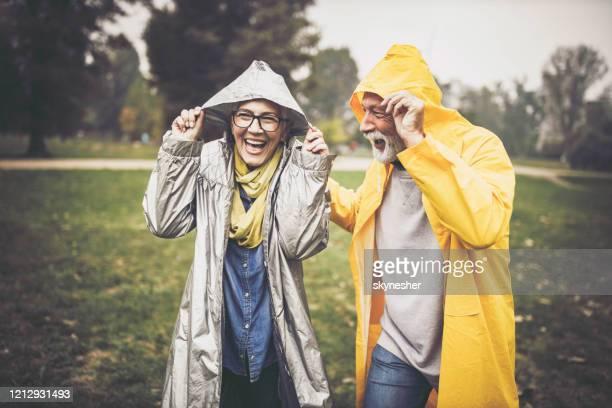happy senior par i regnrockar under regnig dag i naturen. - regn bildbanksfoton och bilder