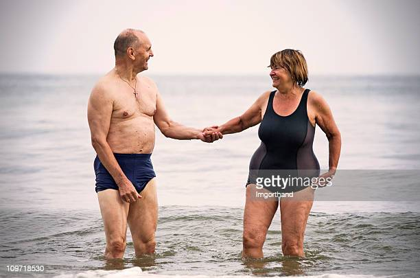 happy senior couple in sea - wading stock pictures, royalty-free photos & images