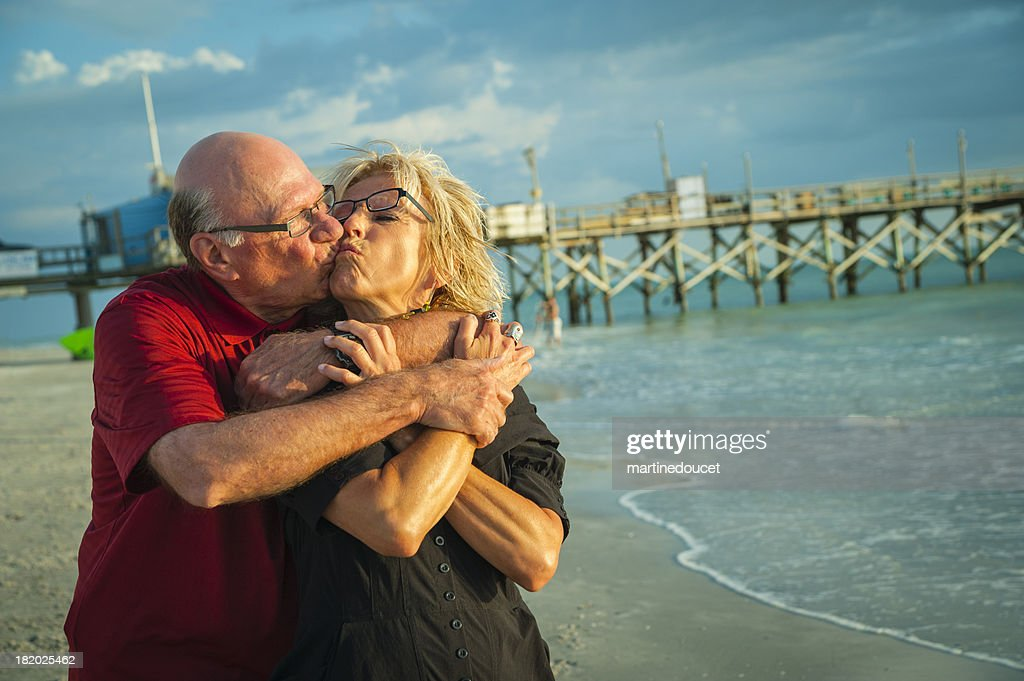 Happy senior couple kissing on the beach at sunset. : Stock Photo
