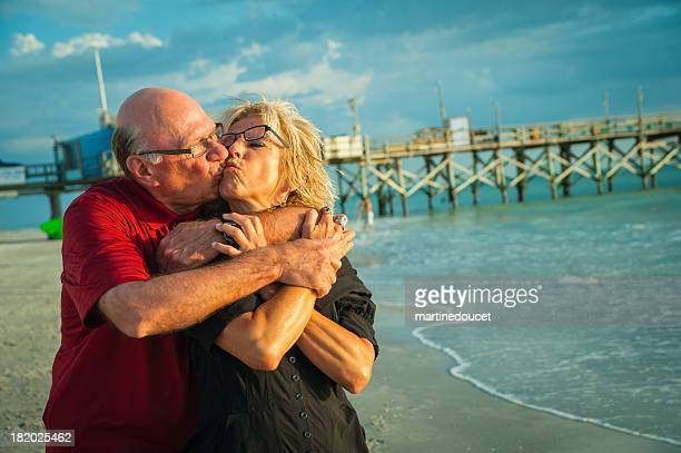 Happy senior couple kissing on the beach at sunset.