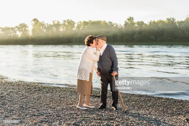 Happy senior couple kissing on the beach