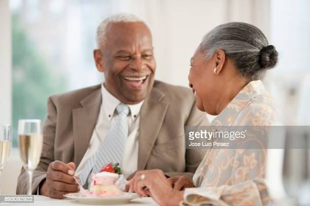 Happy senior couple laughing and eating cake