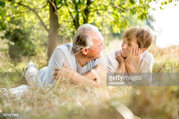 Happy senior couple lying in meadow