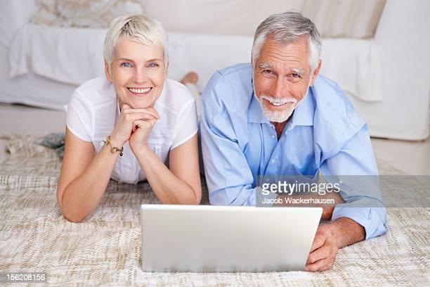 Glücklich altes Paar mit laptop auf dem Boden liegen