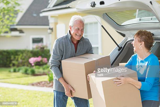 happy senior couple moving boxes in car - layoff stock photos and pictures