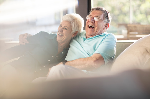 Happy senior couple on couch at home - gettyimageskorea