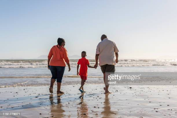 happy senior couple on the beach together with their grandson - western cape province stock pictures, royalty-free photos & images