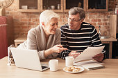 Happy Senior Couple Planning Family Budget Together With Laptop And Papers