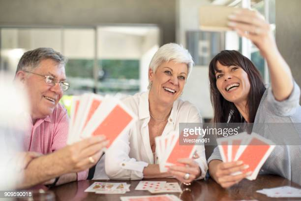 Happy senior couple playing cards and taking a selfie with daughter at home