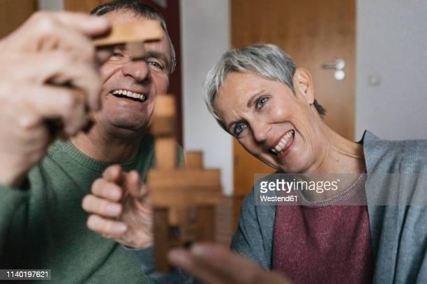 happy senior couple playing dexterity game at home - 55 59 jahre stock-fotos und bilder