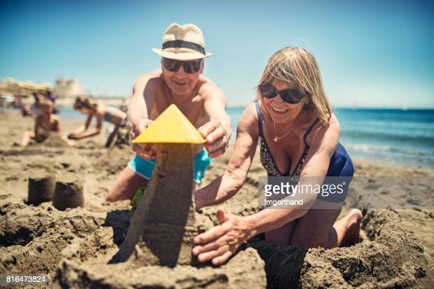Happy senior couple playing in sand on beach