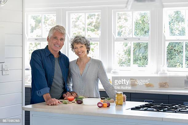 happy senior couple preparing food in kitchen - waist up stock pictures, royalty-free photos & images