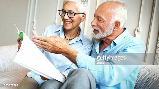 happy senior couple reading a magazine. - brochure stock pictures, royalty-free photos & images