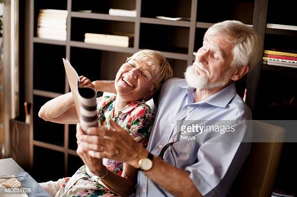 Happy Senior Couple Reading Magazine in Bar