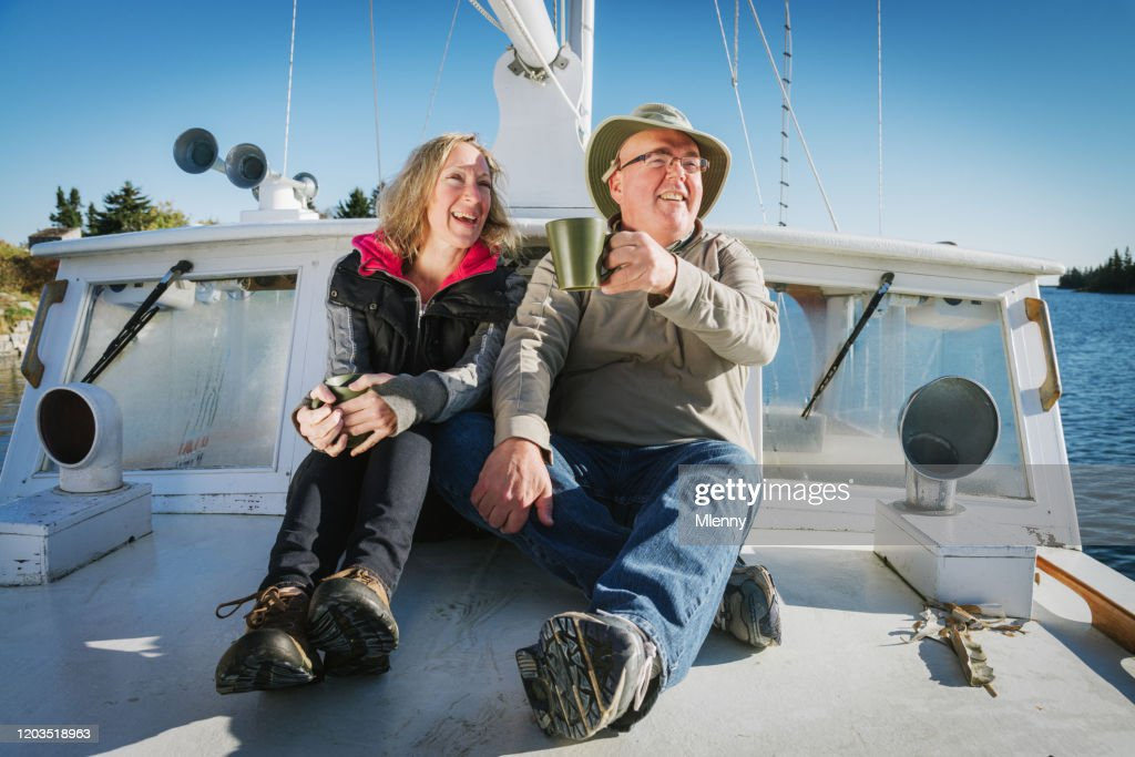 Happy Senior Couple Relaxing On Their Sailboat : Stock Photo