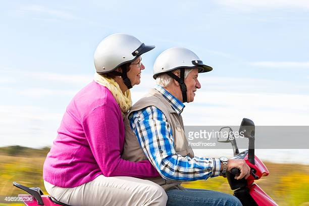 Happy Senior Couple Riding a Motor Scooter