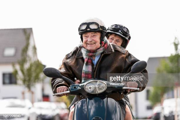 happy senior couple riding motor scooter - hoofddeksel stockfoto's en -beelden