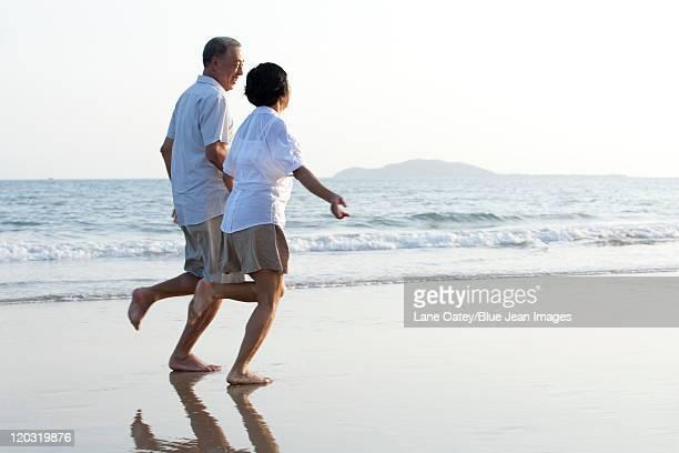 Happy senior couple running on the beach