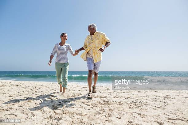 Happy senior couple running on the beach