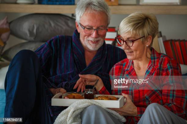 Happy senior couple sharing breakfast in bed
