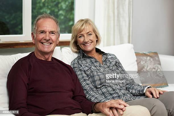 Happy senior couple sitting on sofa in cottage