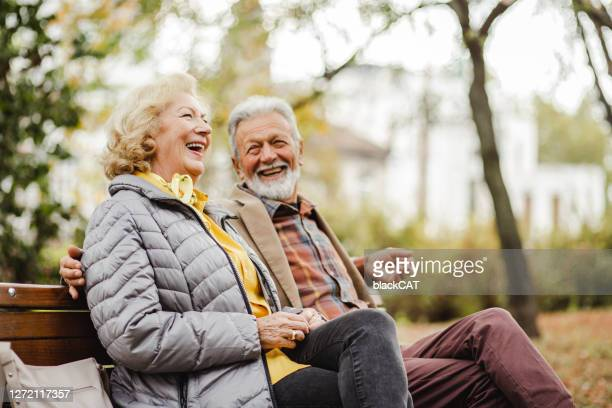 happy senior couple sitting on the bench in park - senior couple stock pictures, royalty-free photos & images