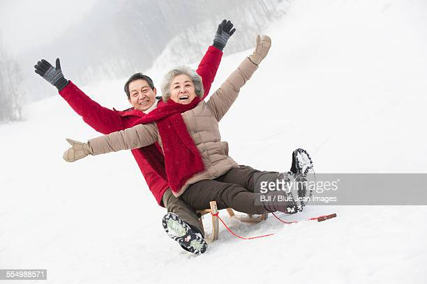 happy senior couple sliding on a sled - harbin winter stock pictures, royalty-free photos & images