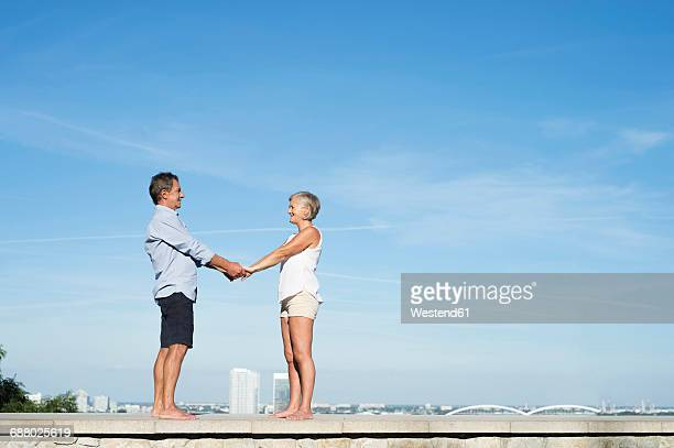 Happy senior couple standing barefoot on a wall in front of sky holding hands