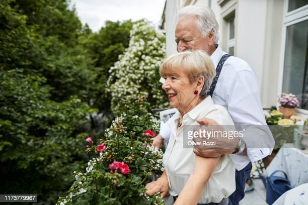happy senior couple standing on balcony at home - wife stock pictures, royalty-free photos & images