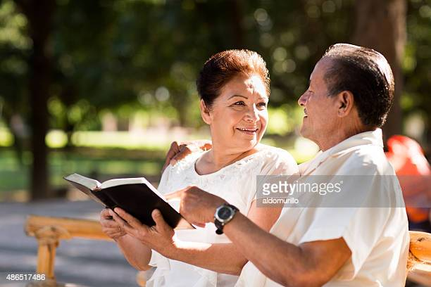 Happy senior couple studying the Bible